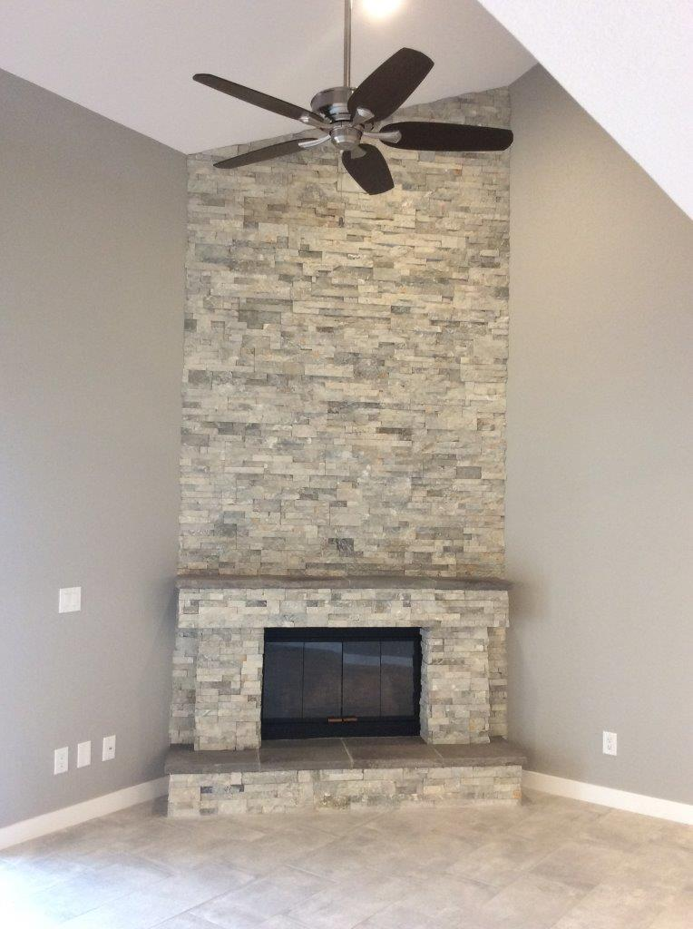Tiled room with fresh paint, fan and fireplace